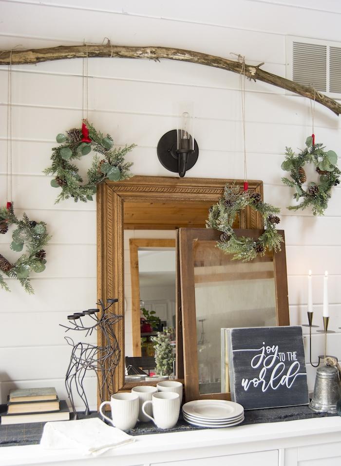 branche de bois flotté avec des couronnes de noel de branches de sapin suspendues, miroirs avec cadre bois sur mur blanc