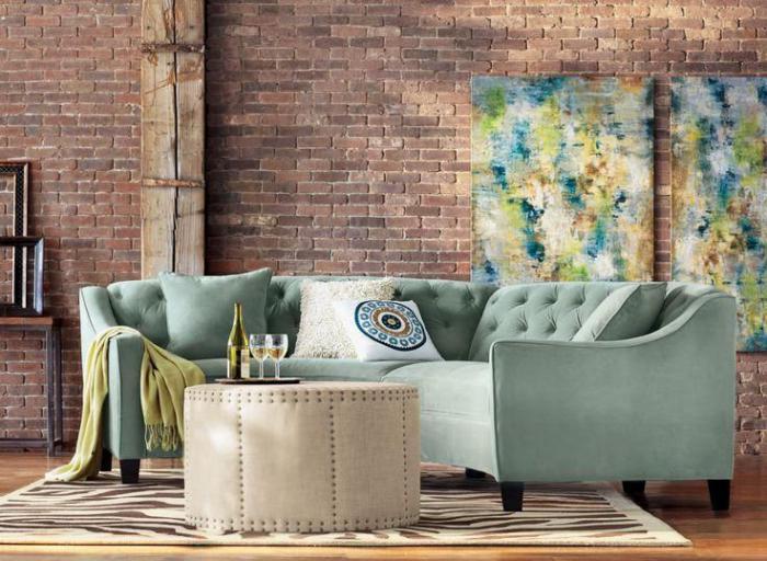 canapé-arrondi-tableaux-peinture-abstraite-mur-briques