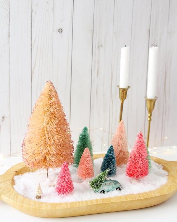 idee de centre de table noel original, plateau de service avec de la neige artificielle, figurines de sapins colorées et bougeoirs dorés