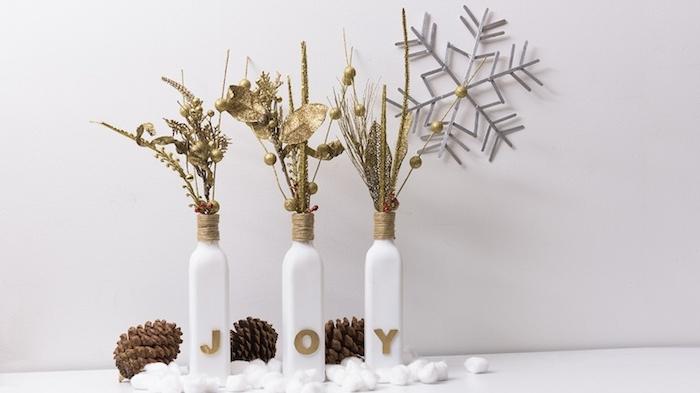 recyclage bouteilles de verre avec ficelle autour le col de la bouteille et petit bouquet en brins vegetation artificielle dorée