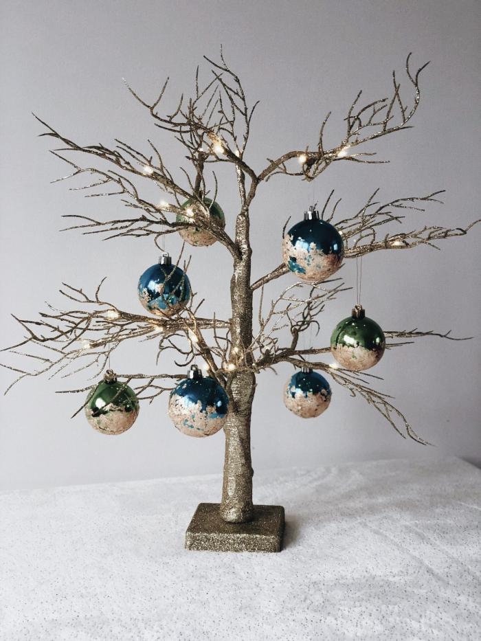 decoration sapin de noel stylée, modèle d'arbre de Noël repeint en glitter doré et décoré avec ornements personnalisés à effet métallique