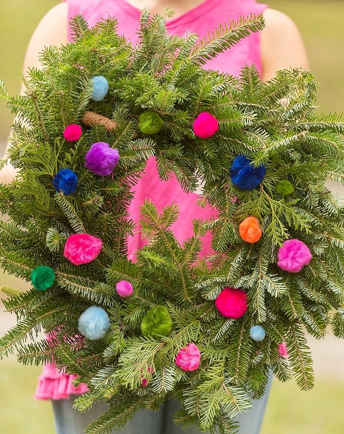 couronne de noel a fabriquer soi meme en branches de sapin naturelles et pompons colorés de tailles variées