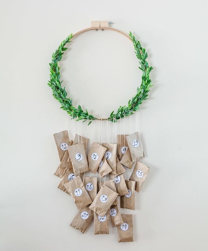 fabriquer un calendrier de l avent couronne de noel en bois et feuillage vert artificiel avec des sachets papier kraft