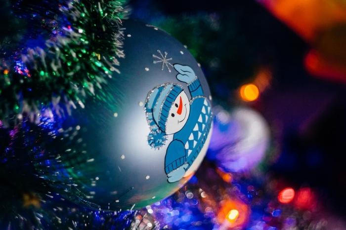 deco de noel a faire soi meme, modèle de boule de sapin peinte en bleu métallique et décoré avec sticker bonhomme de neige