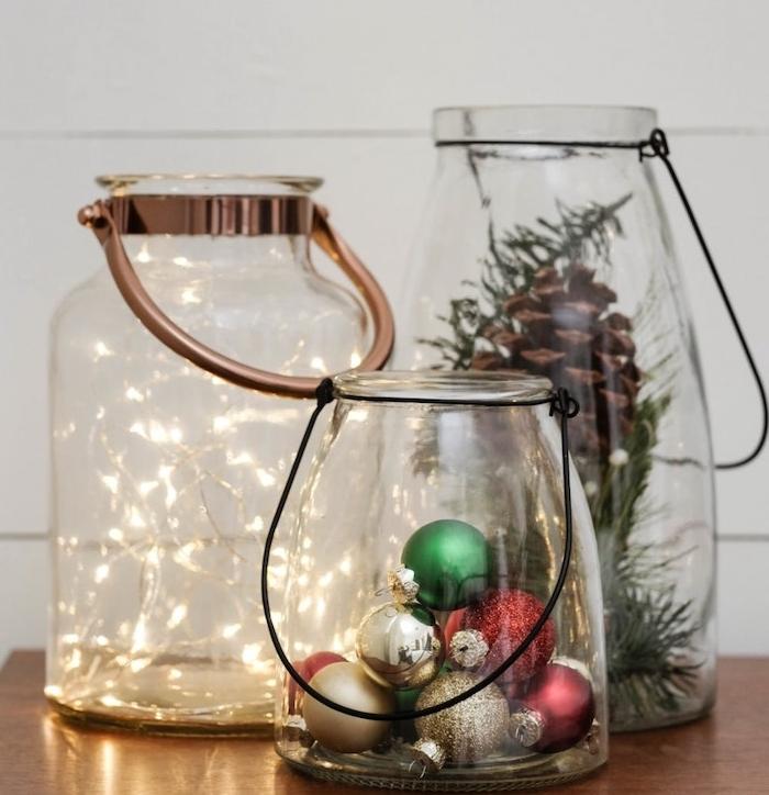 lanternes decoratives en gros bocaux en verre avec manche et deco de guirlande lumineuse, boules de noel, pommes ou branches de pin