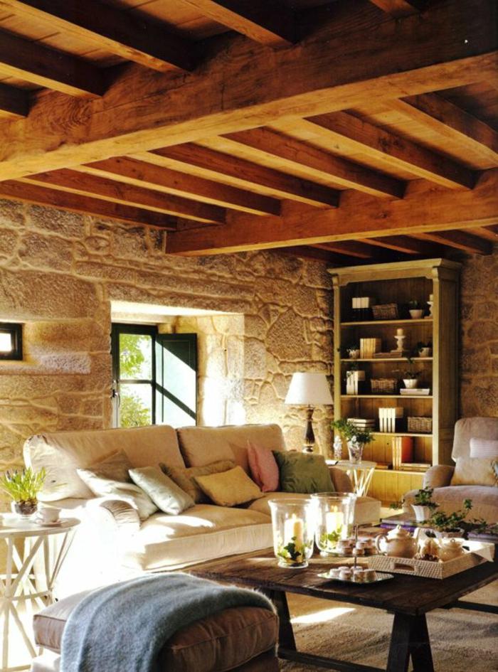 joli-interieur-de-style-rustique-avec-plafond-en-combles-en-bois-mur-en-pierres-canape-beige
