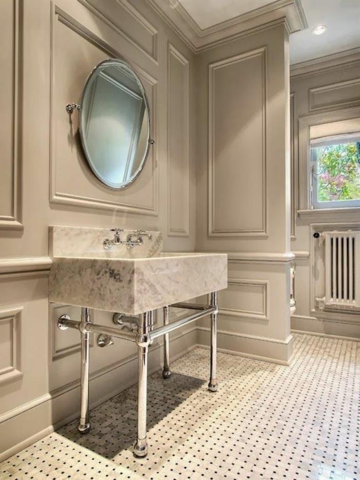 joli-salle-de-bain-avec-murs-gris-et-sol-a-points-noirs-miroir-rond-et-lavabo-en-marbre
