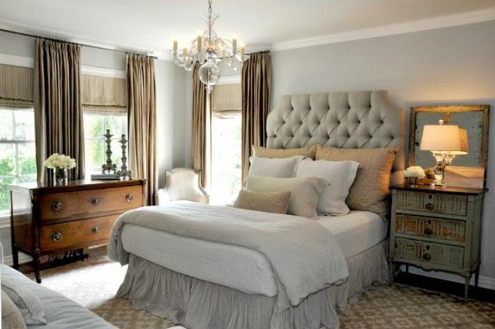 jolie-chambre-a-coucher-avec-tete-de-lit-matelassée-et-rideaux-longs-beiges-lustre-moderne