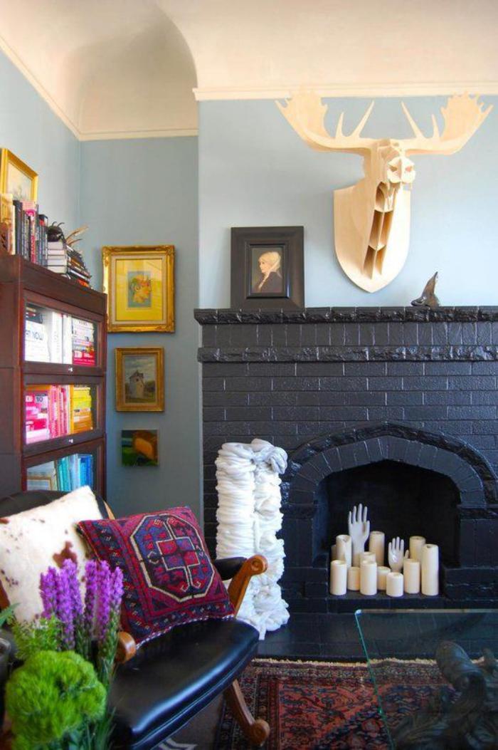 manteau-de-cheminée-noir-et-sculptures-extravagantes-blanches