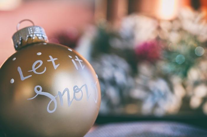 exemple de boule de noel transparente customisée avec peinture métallisée en or et dessins blancs à motifs Noël