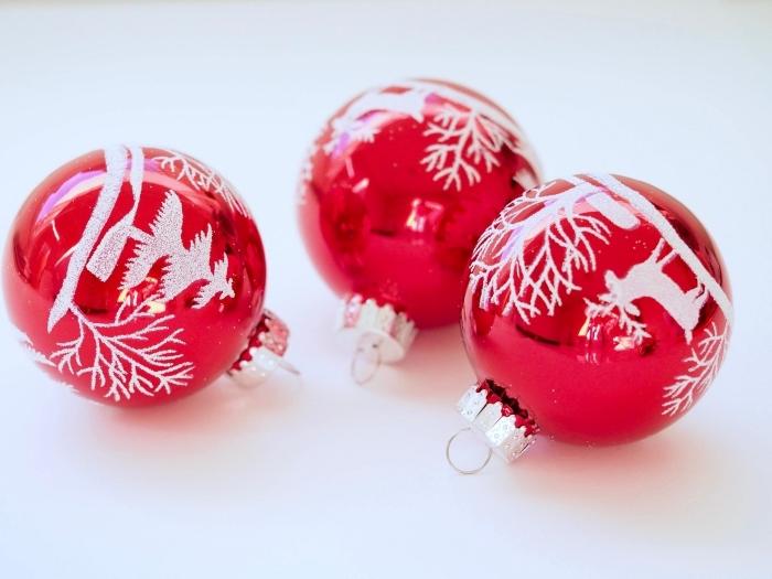 bricolage de noel facile, diy boules de sapin rouges décorées avec dessins à motifs sapins et cerfs de Noël en peinture glitter blanche