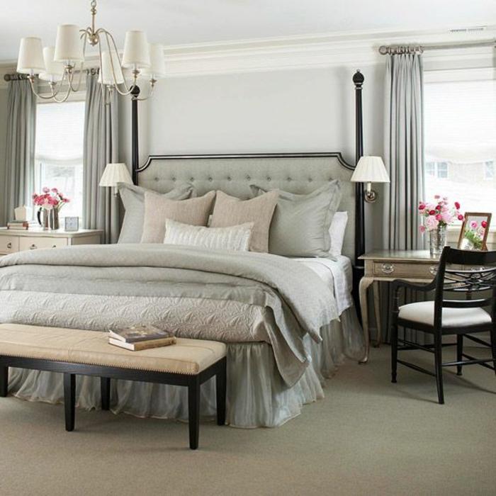 tete-de-lit-captionnée-en-cuir-gris-et-lustre-blanche-moquette-beige-dans-la-chambre-a-coucher