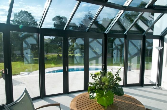 0-bioclimatique-veranda-en-verre-table-en-bois-foncé-belle-vue-vers-le-jaridn-pelouse-verte