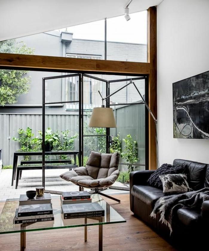 1-les-portes-pliantes-pour-le-salon-moderne-un-canape-noir-en-cuir-et-sol-en-bois-foncé-lampe-de-salon-blanche