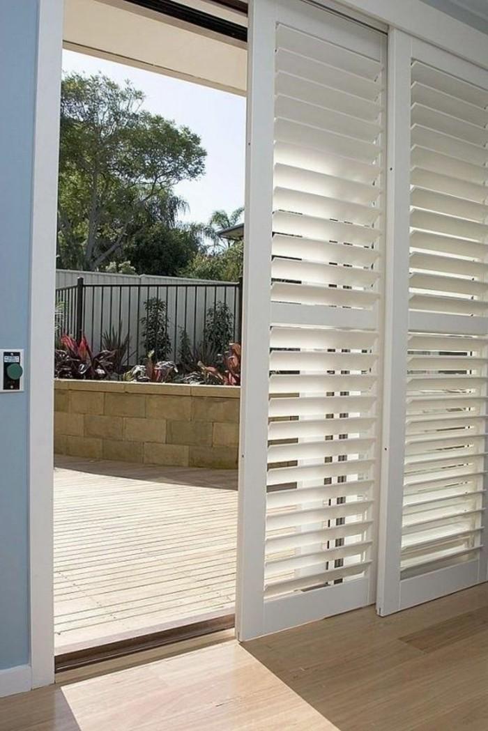 porte-coulissante-en-bois-de-couleur-blanc-vers-le-jardin-devant-la-maison-moderne