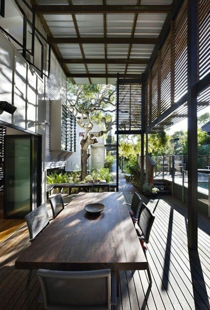 terasse-bioclimatique-veranda-bioclimatique-pergola-bioclimatique-et-sol-en-parquet-foncé-table-et-chaises-en-bois