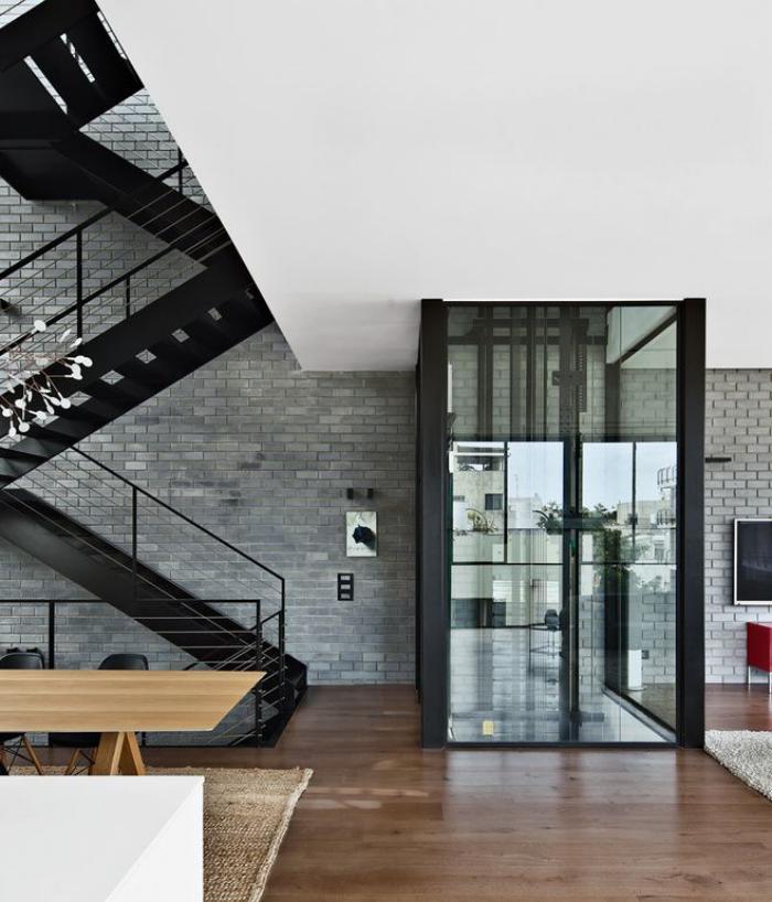 escalier-suspendu-métallique-mur-en-briques-grises