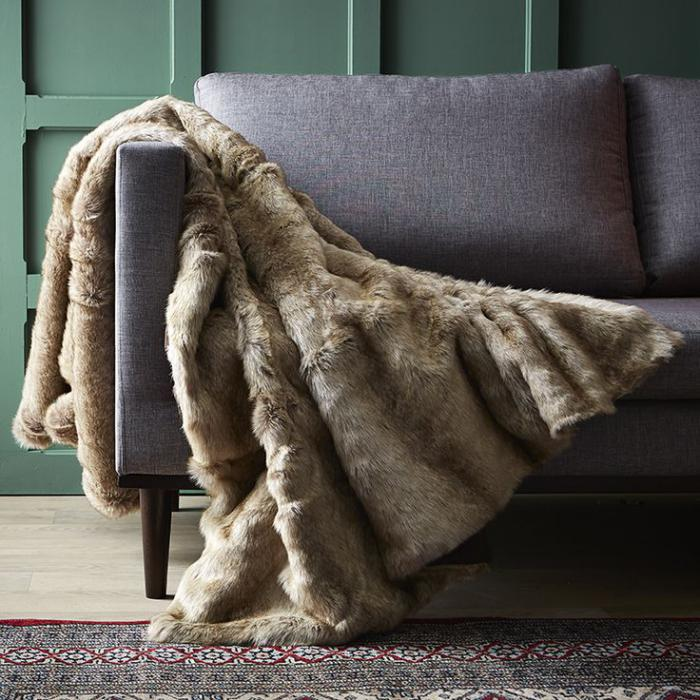 plaid-fausse-fourrure-beige-sur-un-sofa-gris