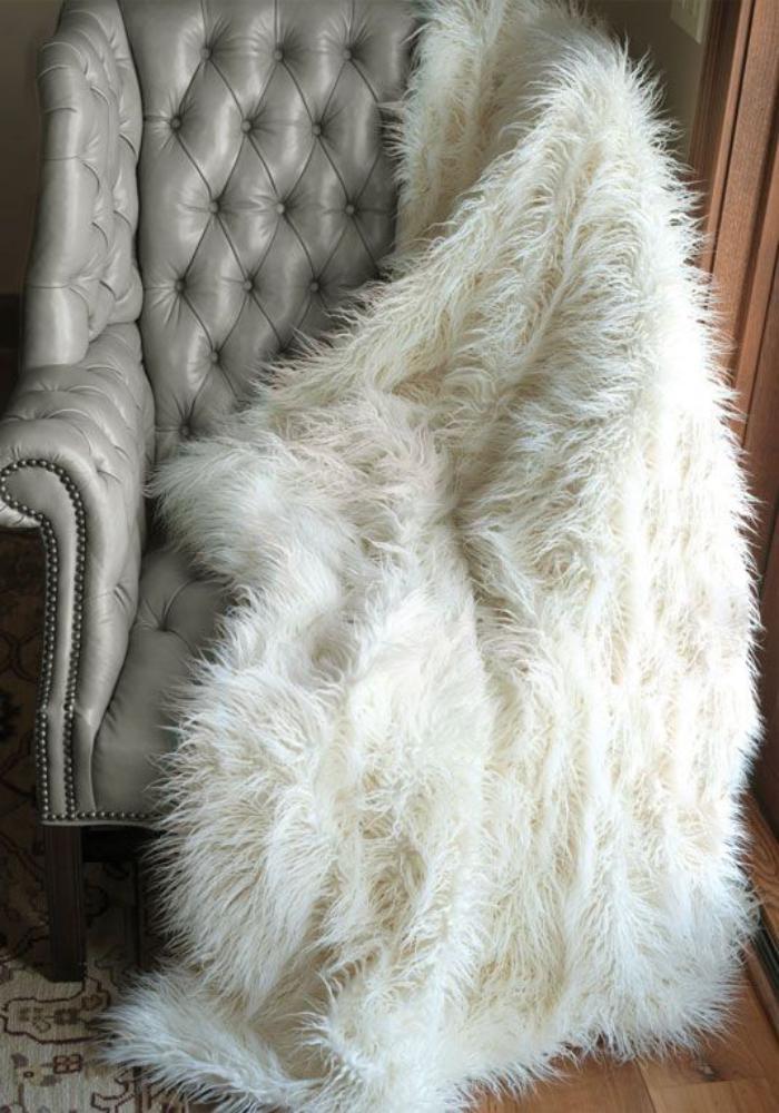 plaid-fausse-fourrure-fauteuil-gris-capitonné