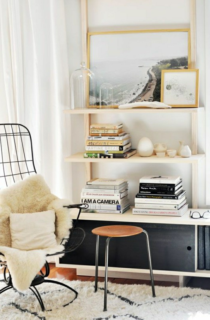 Biblioth?que Bois Clair : bibliotheque murale en bois clair et tapis beige, chaise en fer, mur