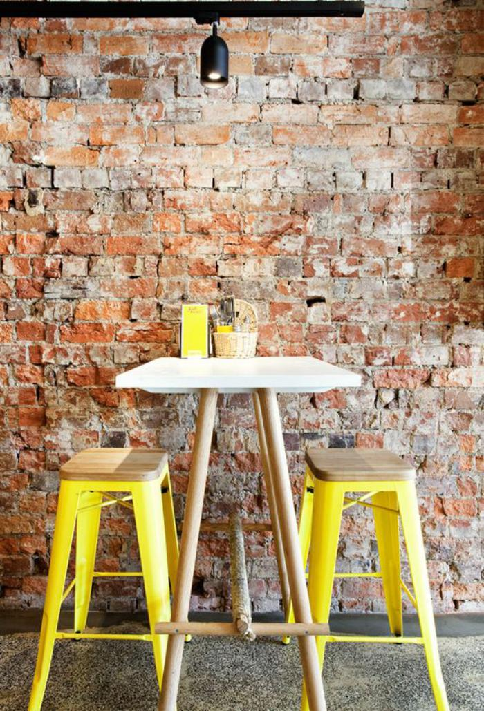brique-rouge-décor-mur-en-briques-avec-tabourets-jaunes