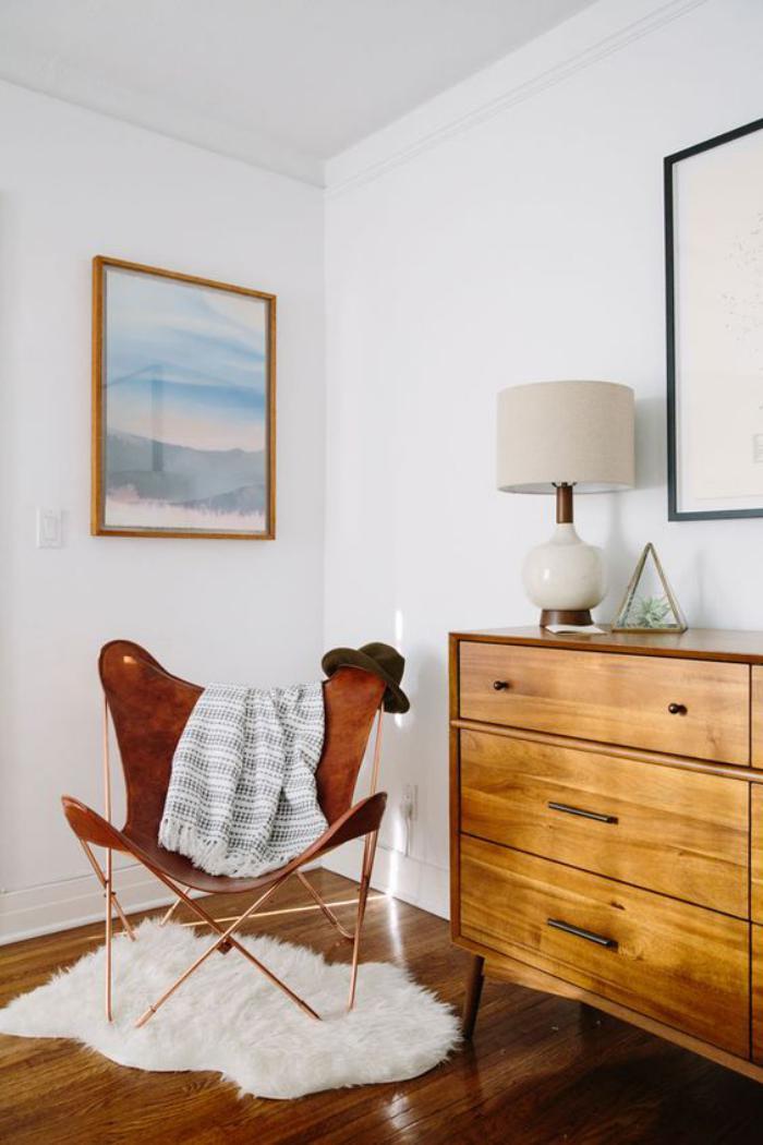 chaise-papillon-et-commode-vintage-dans-une-petite-chambre-blanche