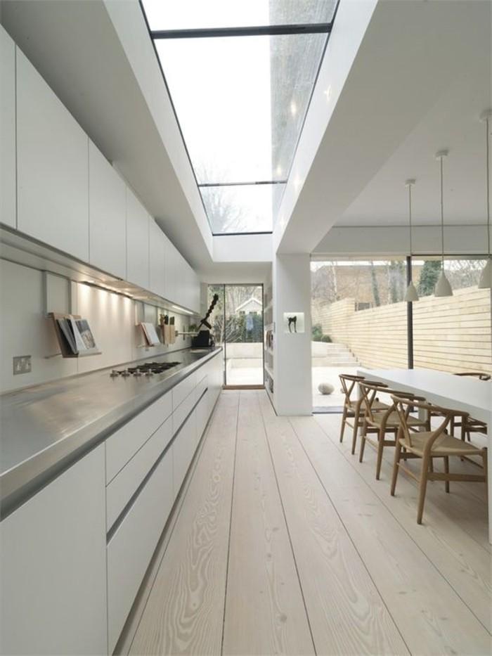 cuisine-taupe-avec-sol-en-parquet-clair-et-grande-table-avec-chaises-fenêtre-de-toit-velux