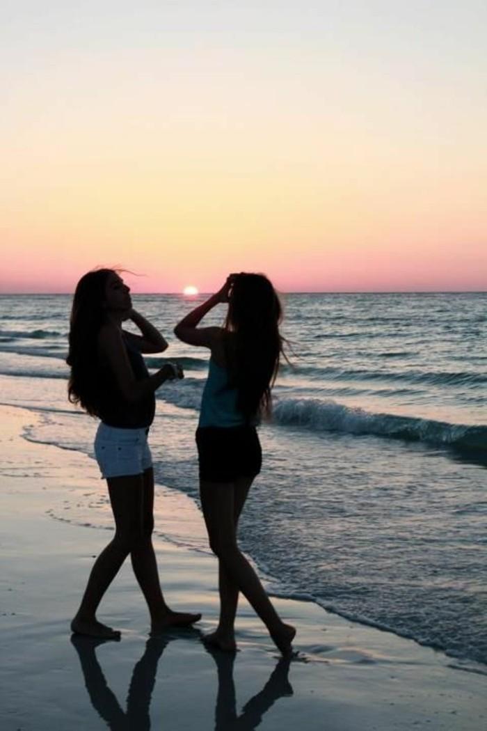 filles-qui-marchent-sur-la-plage-photo-plage-paradisiaque-couche-du-soleil