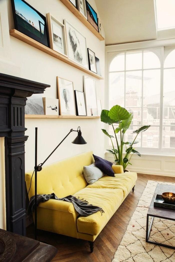 grande-canape-de-salon-jaune-tapis-beige-parquet-en-bois-foncé-plantes-vertes-d-interieur