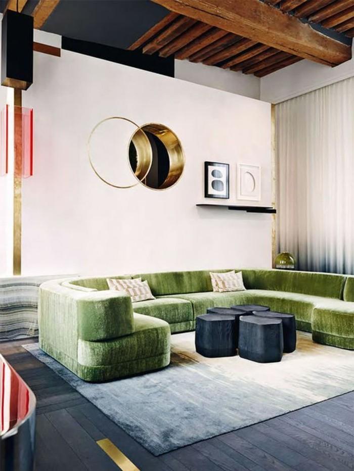 joli-canape-d-angle-arrondi-de-couleur-vert-tapis-beige-murs-beiges-salon-moderne