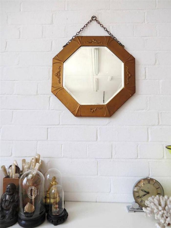 miroir-doré-octogonal-accroché-à-un-mur-blanc