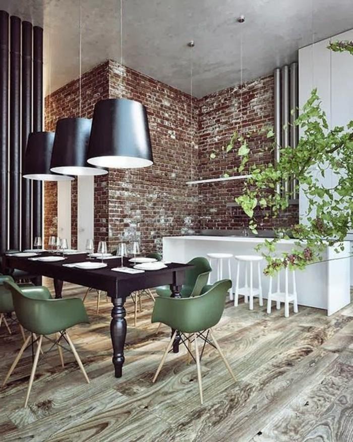 salle-à-manger-design-avec-murs-de-briques-rouges-sol-en-parquet-clair-chaise-de-table-vertes