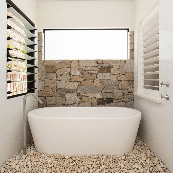 salle-de-bain-ultra-chic-baignoire-blanche-murs-en-pierres-beiges-baignoire-balnche