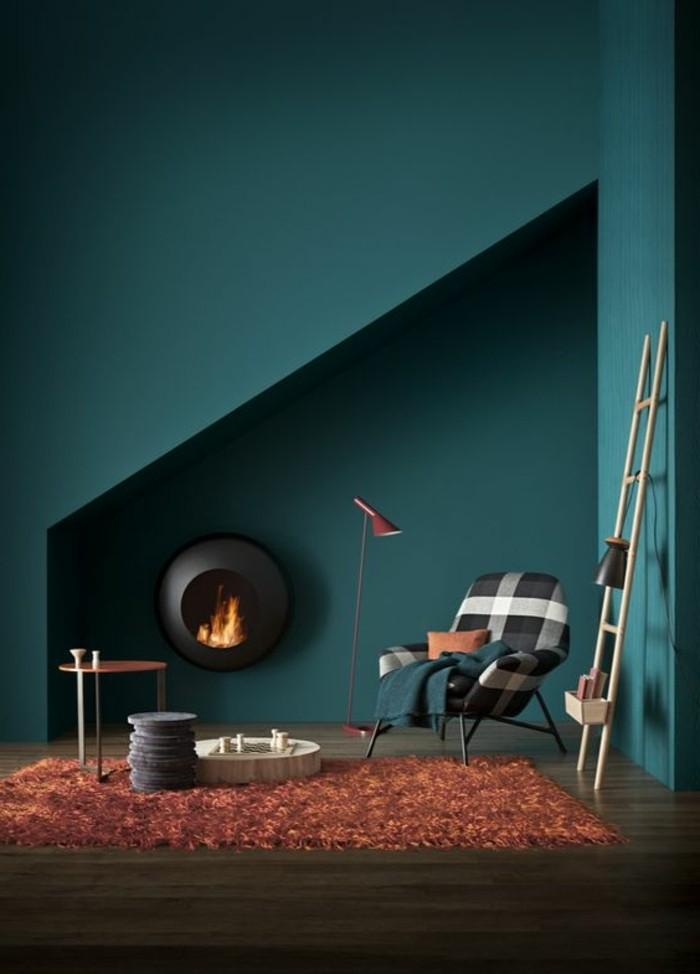 salon-avec-murs-de-couleur-bleu-foncé-tapis-orange-sol-en-parquet-foncé-lampe-de-lecture-rouge