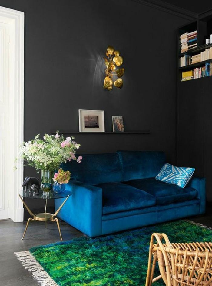 salon-chic-tapis-vert-canapé-bleu-foncé-chaise-en-rotin-bois-clair-meubles-de-salon