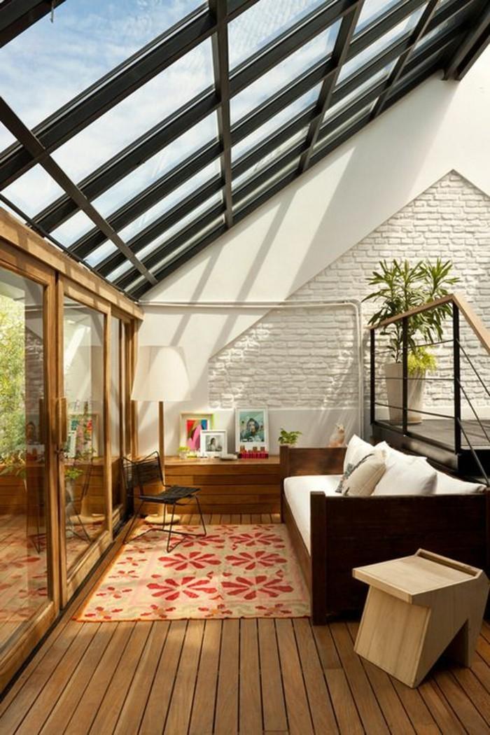 salon-plafond-en-verre-canapé-beige-tapis-motifs-florals-sol-en-planchers-marron-foncés