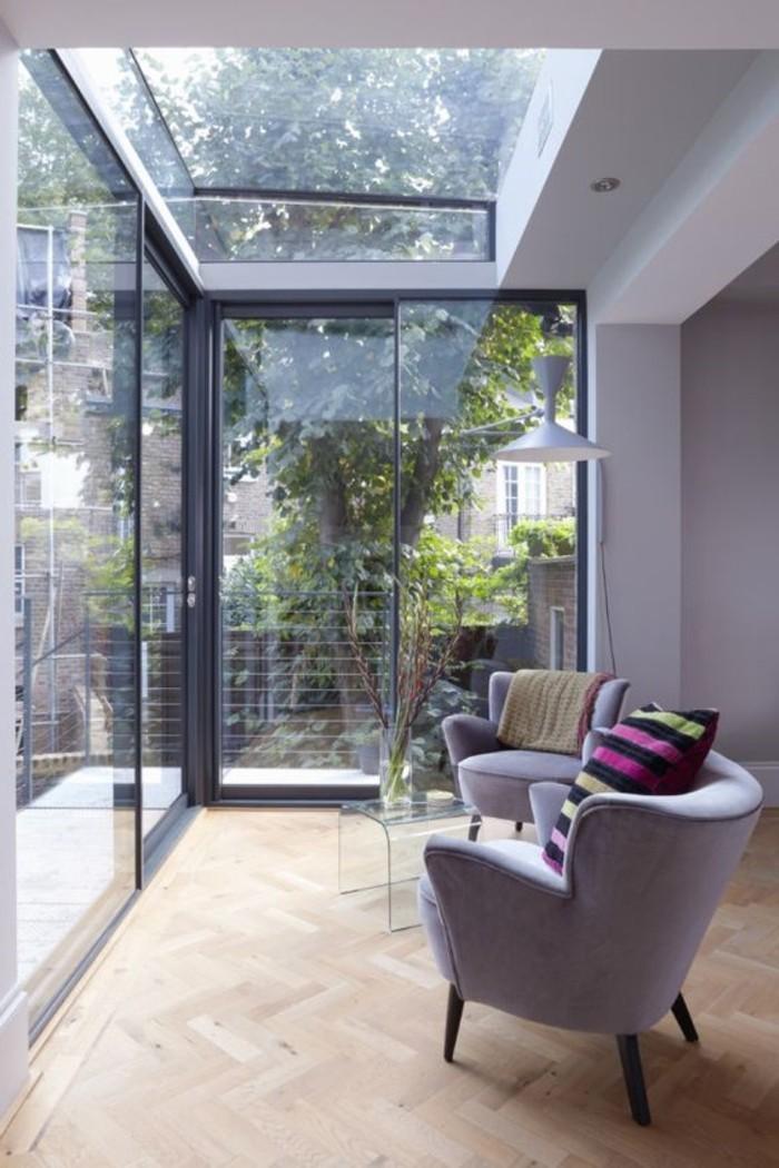 véranda-en-verre-fenêtre-de-toit-velux-verrière-de-véranda-fauteuils-gris