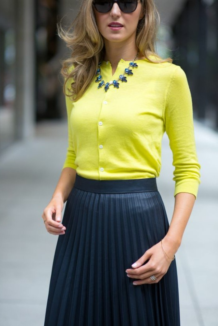 blouse-jaune-femme-en-combinaison-avec-jupe-noire-plissée-cheveux-bonds