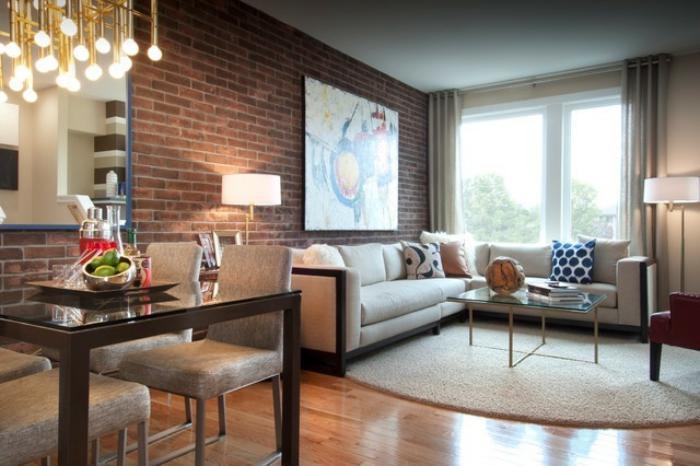 briques-de-parement-tapis-oval-blanc-table-transparente-et-canapé-d'angle
