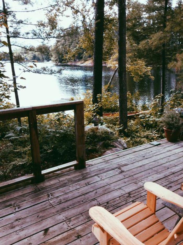 cabane-dans-les-bois-une-véranda-en-bois-vue-vers-un-lac