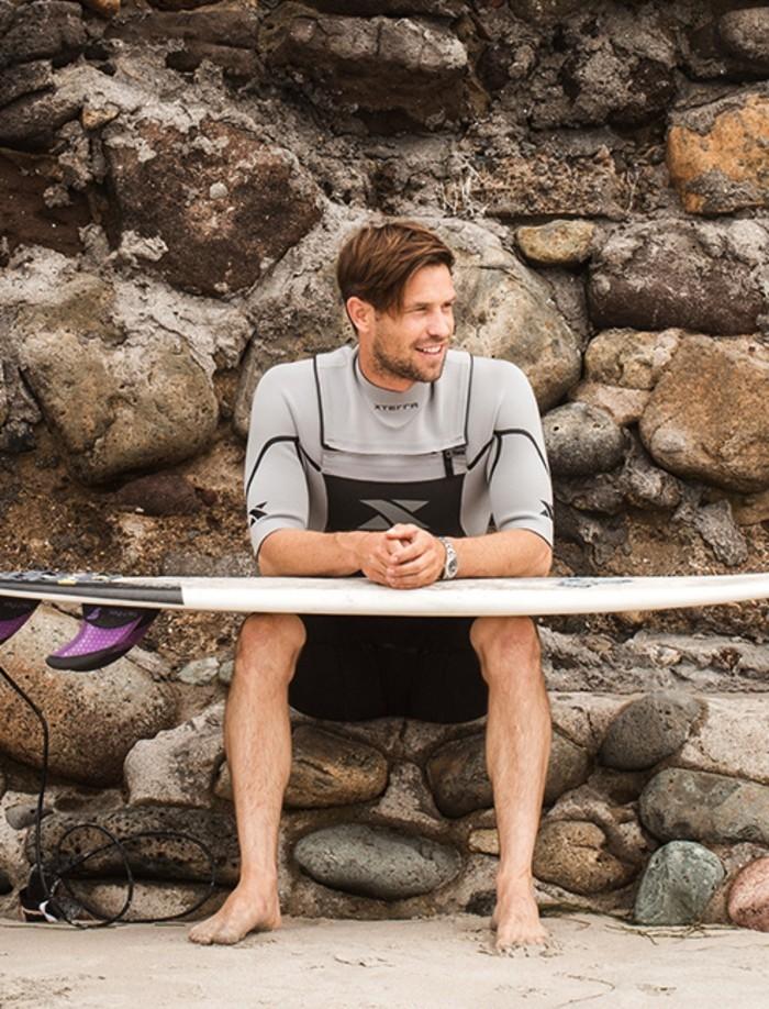 rip-curl-femme-combinaison-surf-pas-cher-s-habiller-bien-confort-a-la-plage-homme-beau-assis-sur-pierre