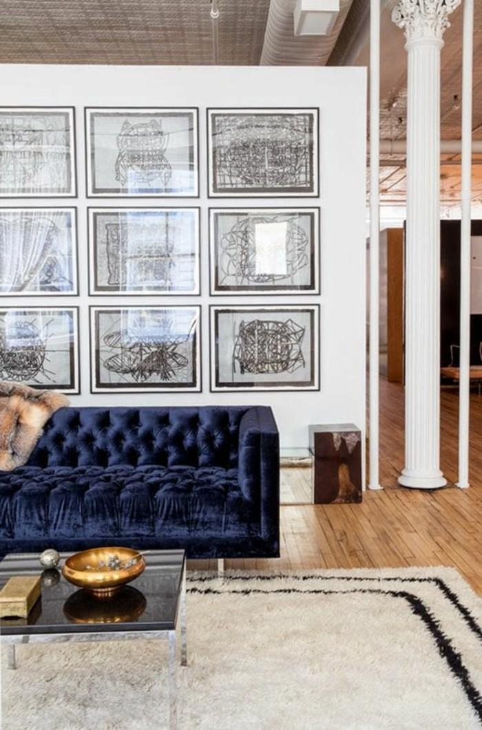 salon-sol-en-parquet-clair-tapis-beige-canapé-bleu-foncé-murs-blancs
