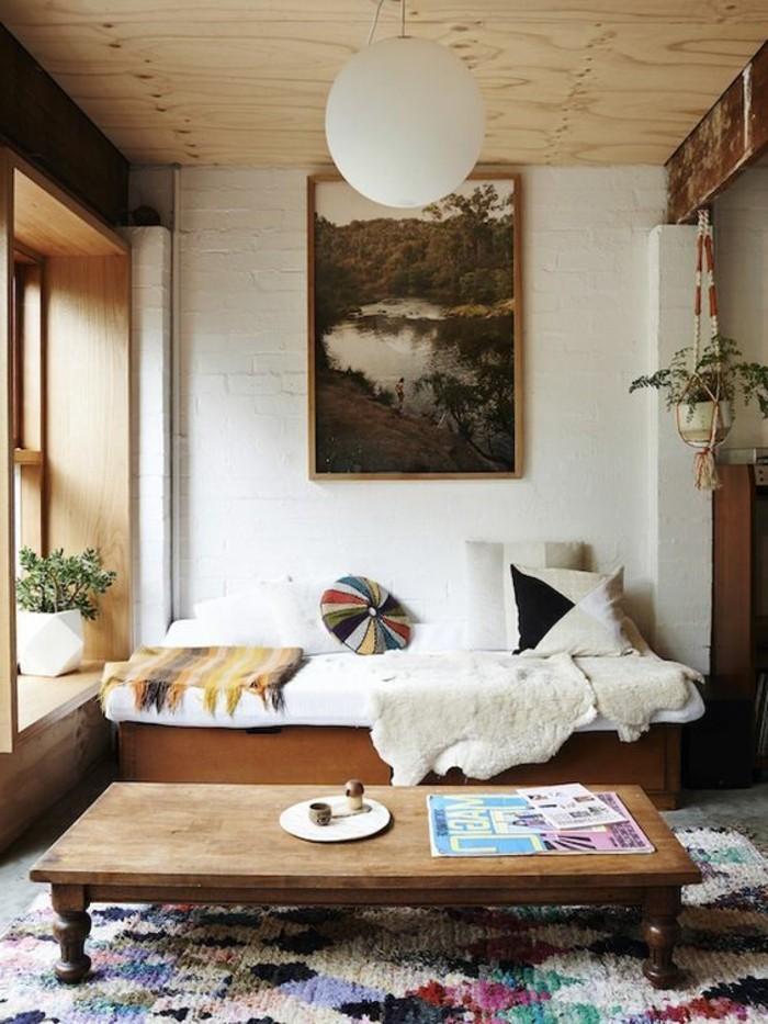 table-basse-en-bois-clair-tapis-coloré-mur-en-briques-blancs-aménager-un-petit-salon