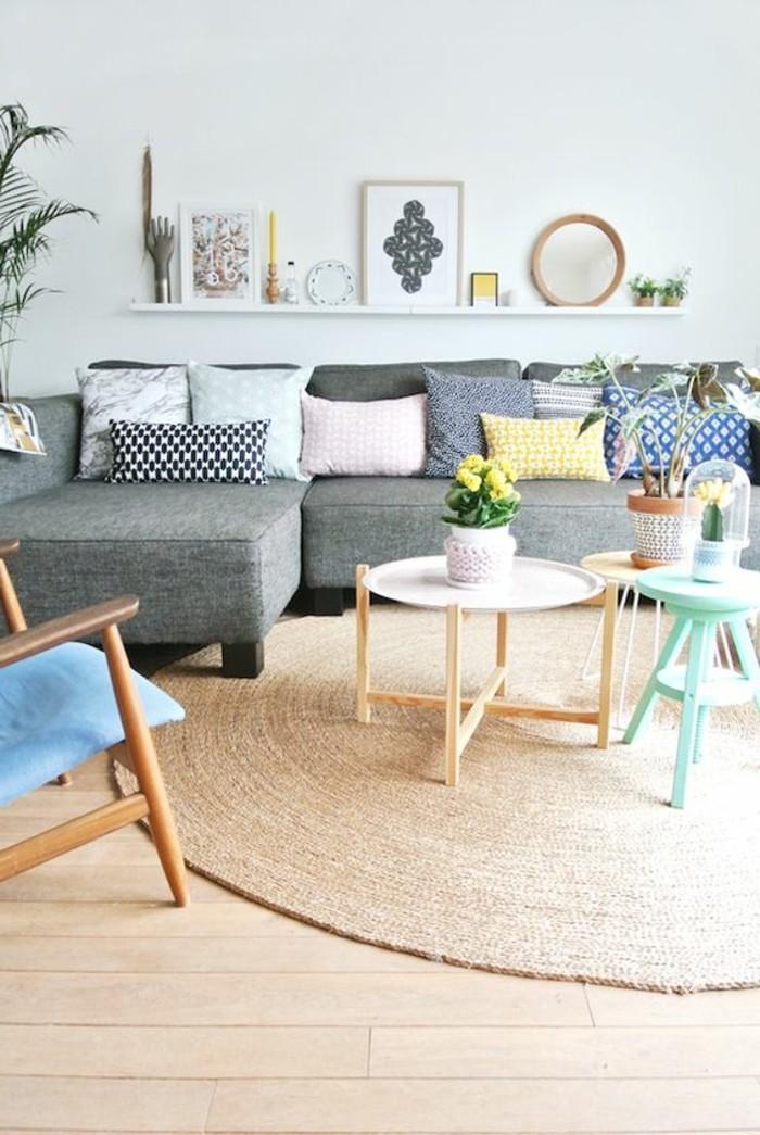 tapis-en-rotin-beige-meubles-en-bois-clair-canape-gris-avec-coussins-colorés-murs-blancs