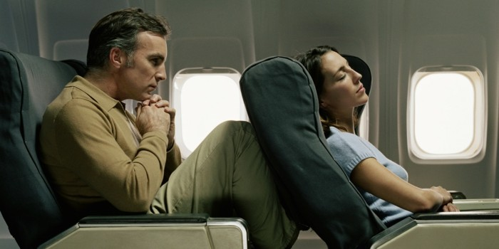 Male passenger with knees against female passenger's seat on aeroplane