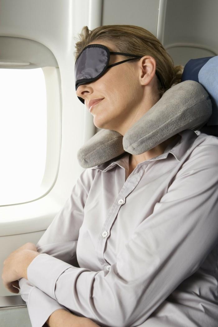 Woman sleeping on plane wearing eye mask