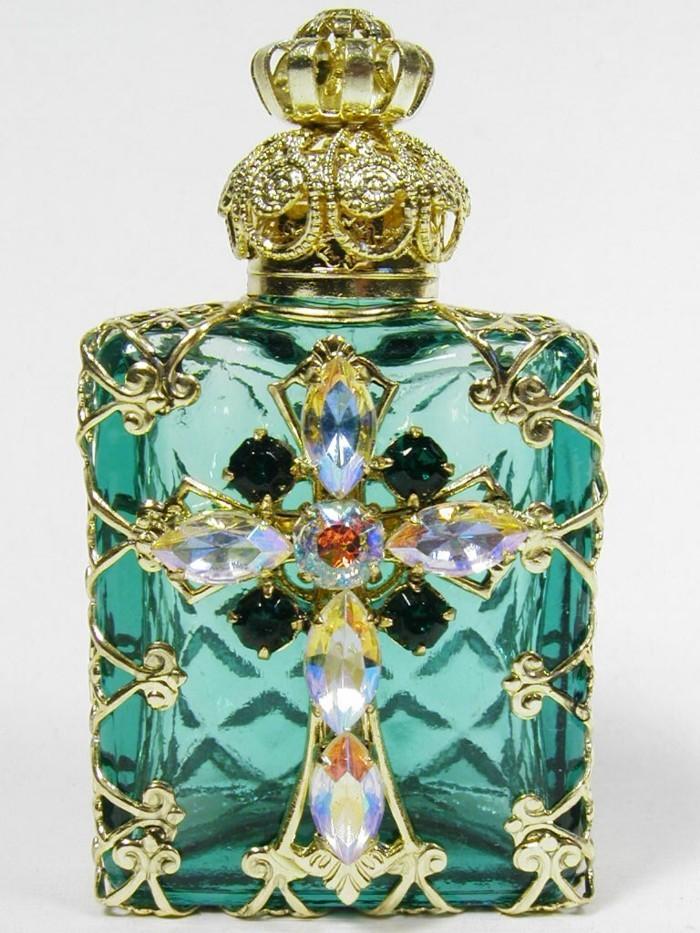 flacon-de-parfum-fond-vert-avec-une-croix-aux-pierres-resized