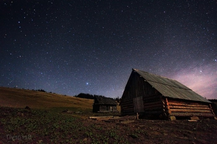 night sky with stars and wooden rural shack on the hill