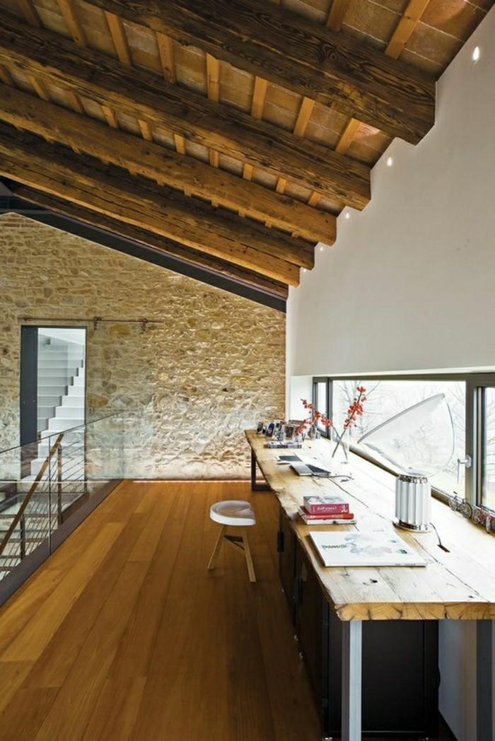 interieur-de-chalet-avec-mur-en-pierres-blancs-plafond-sous-pente-en-bois-clair-combles-chalets-resized