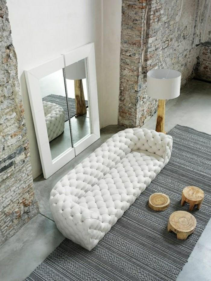 interieur-salon-avec-murs-en-pierres-canape-capitonnée-blanc-en-cuir-blanc-tapis-gris-resized